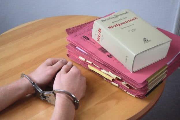 Handschellen und Gesetzbuch auf einem Tisch